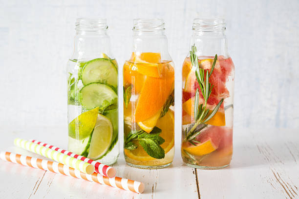 Selection of infused water in glass bottles, white wood wood background, copy space